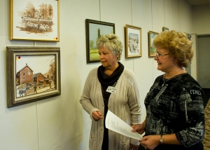 Society President Linda Kale and guest Bette Schmitt view one of Robert Enlow's many landscapes.